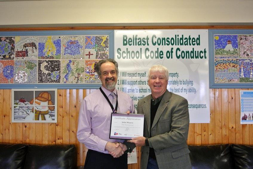 Garth Wade presents Belfast principal John Munro with a certificate of appreciation.