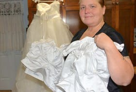 Mindy Ashwood shows some of the angel dresses she has made to date. In the background is a wedding dress, which was never worn and still has its tags, that was donated by a woman who suffered a miscarriage and who wants her dress turned into angel dresses.