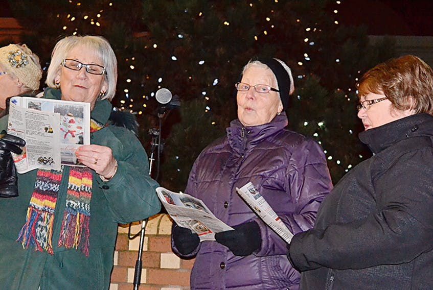 Phyllis Matthews, from left, Wanda Matthews and Norma Getson lead the carolling during the Western Hospital Healthcare Auxiliaryís Lights of Hope ceremony. Bulbs were placed on the tree in memory of, and in honour of, loved ones. The Lights of Hope campaign this year raised $1,871, which the auxiliary is applying towards its share of the cost of a new point-of-care ultrasound machine.  ©THE JOURNAL PIONEER