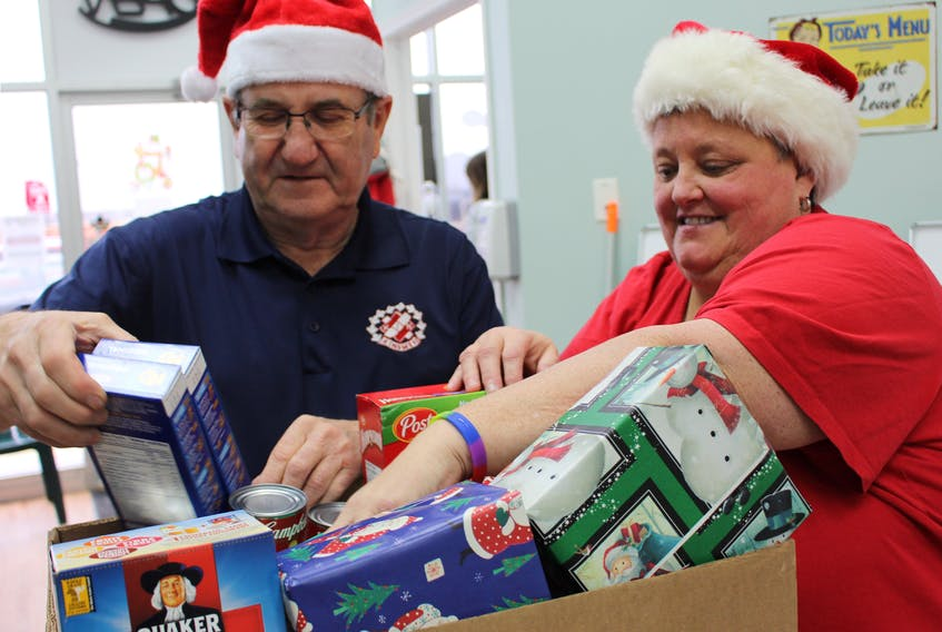 Eric Ferrish, left, and Sue Gallant, pack a box of non-perishables and presents for the annual Kin Appeal, by the Kinsmen and Kinettes, which fills about 600 hampers for about 200 local families.