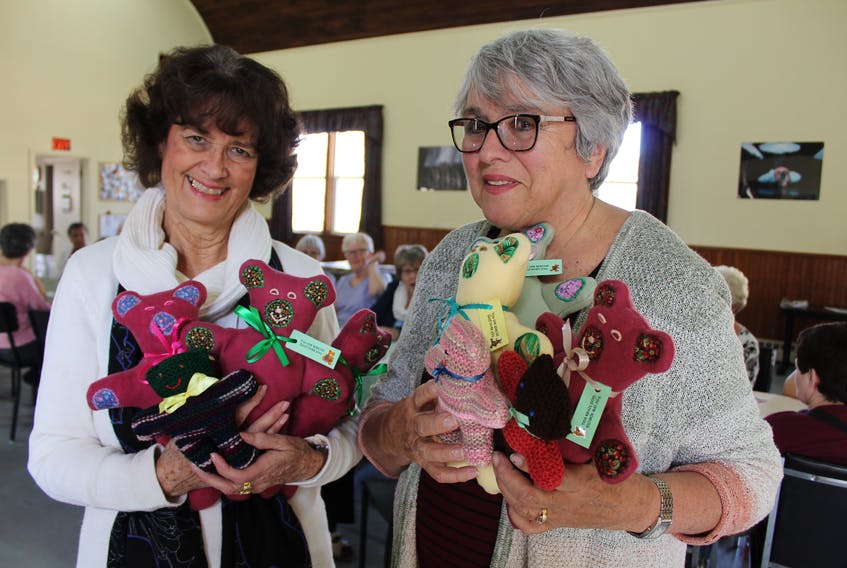 Katie Hickox, left, and Margret Arsenault holds some teddy bears created by Summerside group Kuddles for Kids for children all over the world. Arsenault is a volunteer with the group and Hickox is helping them distribute their creations to a South African community she has worked with in the past.