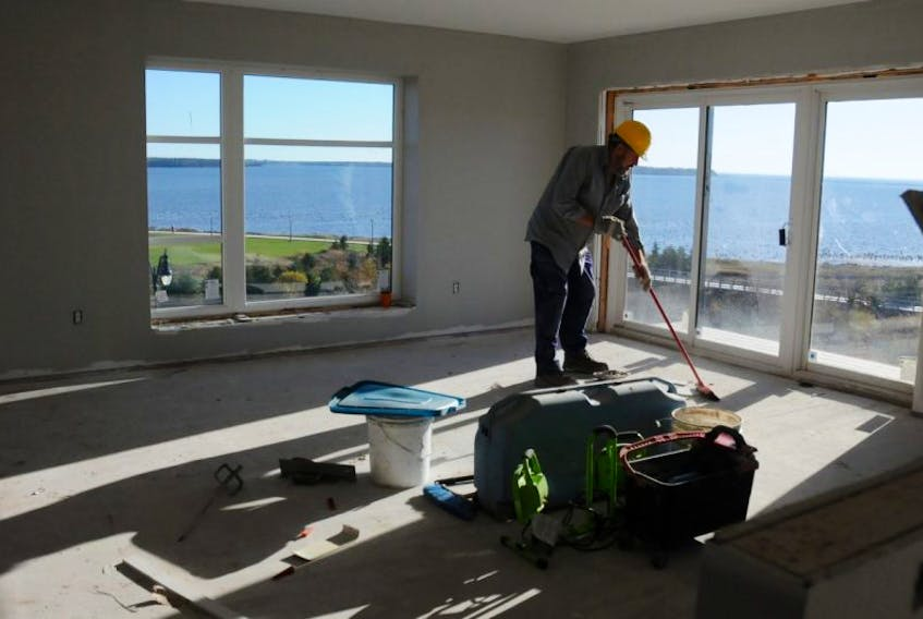 A worker cleans up in the room with the best view of Summerside Harbour in the Tides at Harbour's Edge development on MacKenzie Drive.