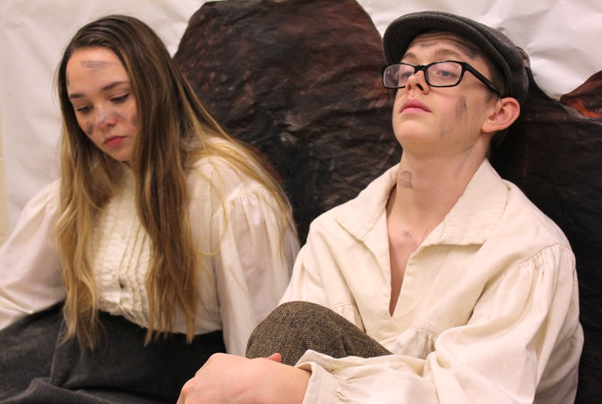 Summerside Intermediate School students Hailey Ahern and Jacob Gallant sit in front of a pile of rubble as characters Arma O'Flaherty and Stuart Oldfield.