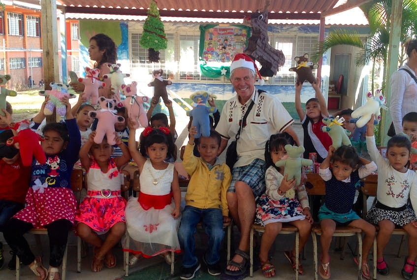 Father Eloi Arsenault, centre, with children of the kindergarten classes in Colonia in Volcanes.