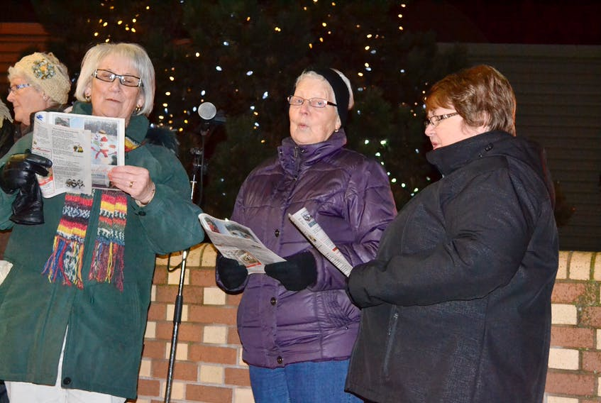 Phyllis Matthews, from left, Wanda Matthews and Norma Getson lead the caroling during the Western Hospital Healthcare Auxiliary's Lights of Hope tree-lighting ceremony Monday night.