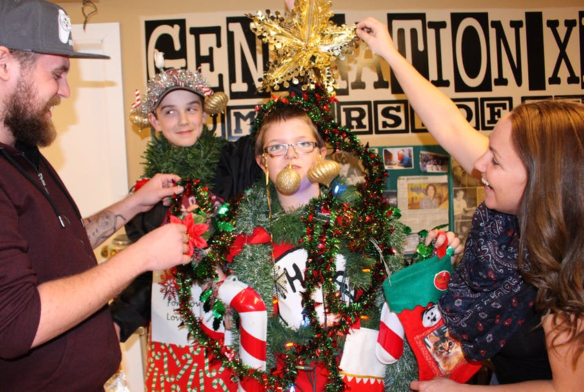 Generation XX staffers Justin Getson, left, and Angie Arsenault, right, help members Rowan Cameron and Josh Grady with their costumes for the upcoming Downtown Summerside Santa Claus parade, which will take place on Nov. 24 at 6 p.m.