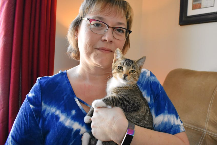 Lori Burnell holds one of the two abandoned feline kittens that were found on the roadside in a red duffel bag.