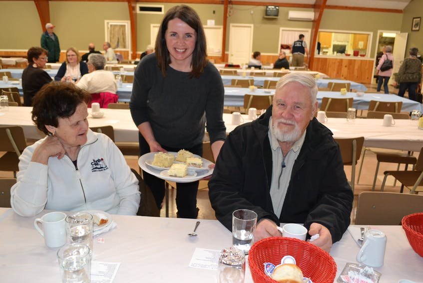 Raeann Kinch tempts North Cape residents Karol and Ralph Arsenault with another helping of dessert following their hot turkey dinner Sunday at the Tignish parish Centre.  A dozen businesses and organizations teamed up to put on the free meal.