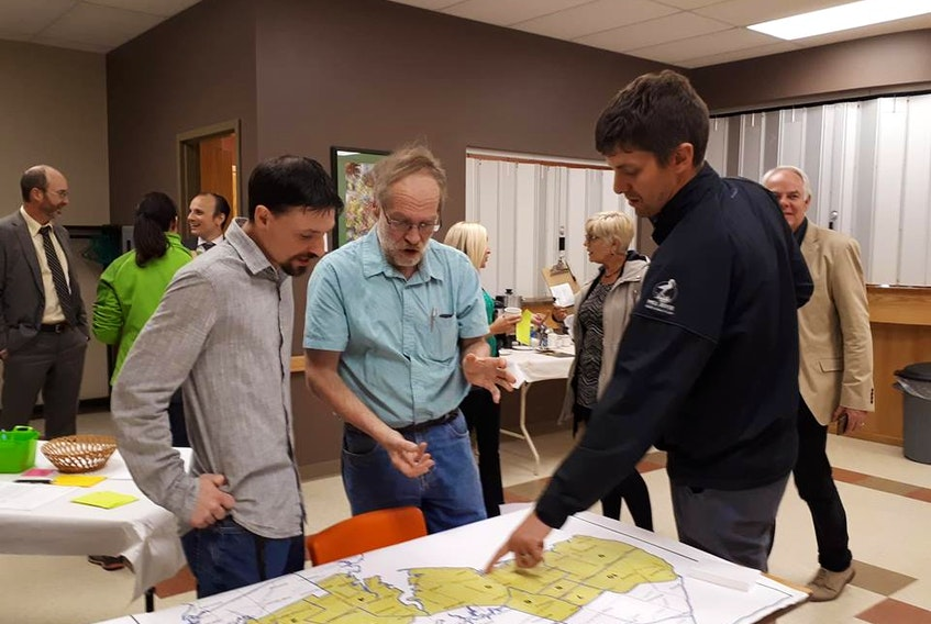 Newly nominated Green candidates Jason Charette for O'Leary-Inverness (left) and Nick Arsenault for Evangeline-Misouche (right) examine electoral maps along with Boyd Leard, Green Party nominated candidate for District 1 (Souris-Elmira).