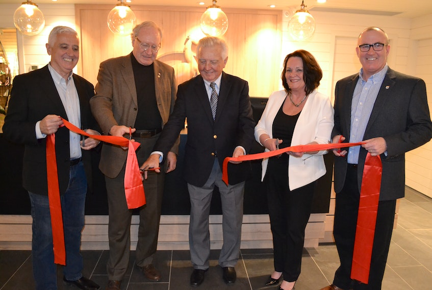 Mill River Resort owner, Don McDougall, center, is accompanied by, from left, Pat Murphy, Minister of Rural and Reginal Development; Premier Wade MacLauchlan, hotel operations manager Louise Arsenault and Economic Development and Tourism Minister Chris Palmer in cutting the ribbon during official opening ceremonies for the renovated resort.