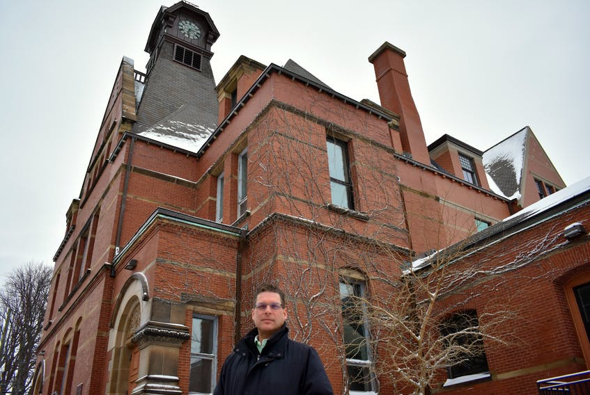 Mike Thususka, director of economic development, stands under the shadow of a 103-year-old clock tower that sits atop City Hall in Summerside. Installing an automated clock winder to keep the time updated is one of the collaborative projects completed by second year students at UPEI and the City of Summerside.