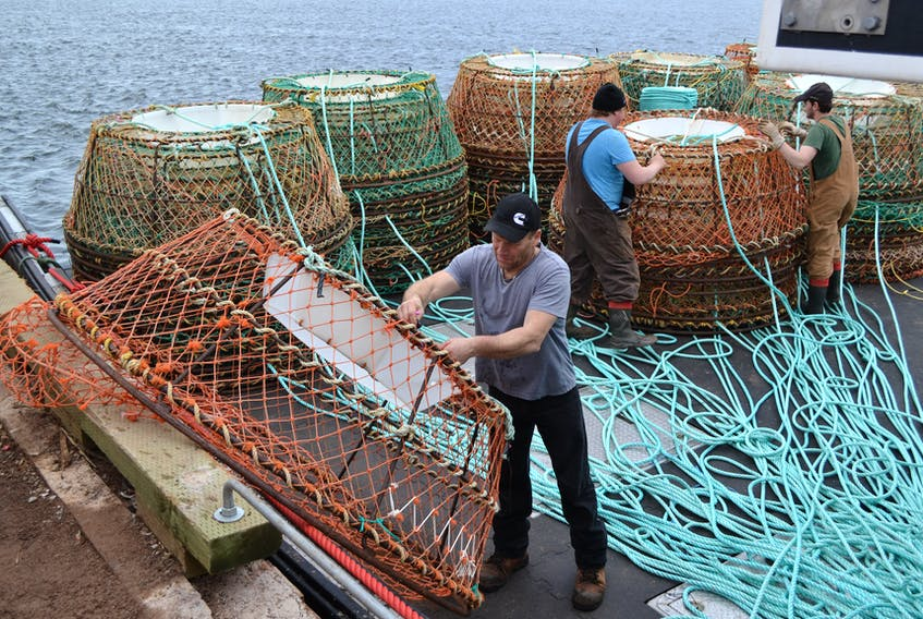Crab fishermen load gear onto a boat at Northport last spring.