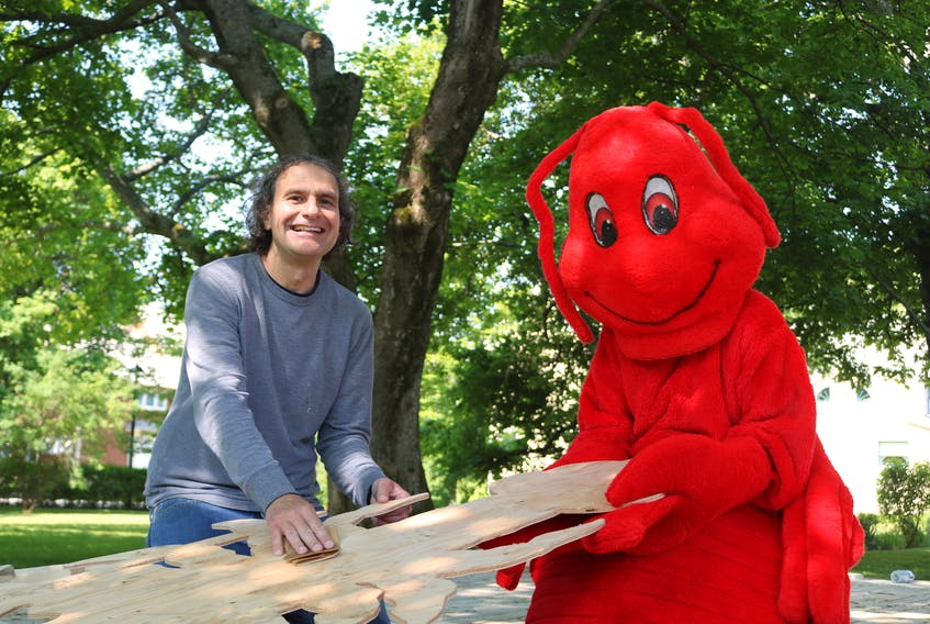 Scott MacLeod, left, gets some help resident lobster at Culture Summerside (Carrie Culleton) on sanding down wooden cutouts of lobsters which will be used for the 63rd annual Summerside Lobster Carnival.