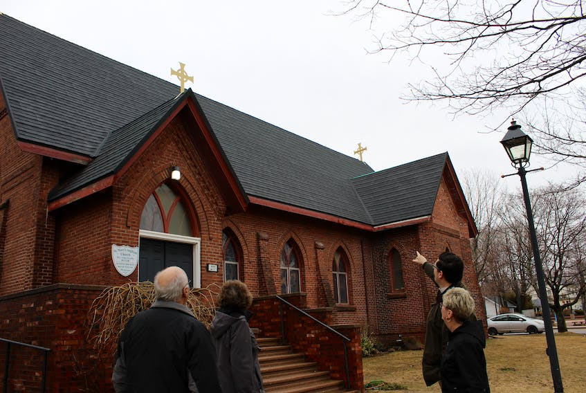 St. Mary's Church rector Rev. Colin Nicolle points to the roof and custom-crafted crosses that were recently installed. The congregation is holding a hymn sing fundraiser in May.