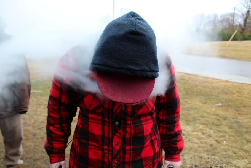 A Three Oaks Senior High student vapes on lunch break.  TOSH recently cracked down on students using e-cigarettes inside the school, this student was in the chained-off designated smoking area at the edge of the parking lot.
