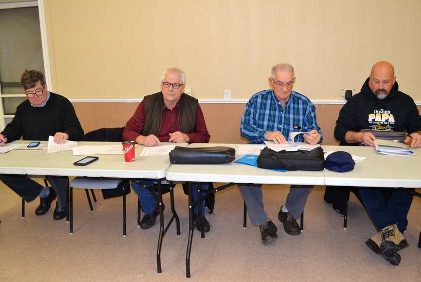 P.E.I. Fishermen's Association managing director, Ian MacPherson, from left, PEIFA president Bobby Jenkins and Prince County Fishermen Association directors Shelton Barlow and Mike Myers review reports during the PCFA's annual meeting Tuesday in O'Leary.
