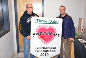 Three Oaks Axewomen head coach Garth Turtle, left, and Three Oaks Senior High School athletic director Joel Arsenault display the championship banner up for grabs at this weekend's 38th Sweetheart senior girls' basketball tournament. Play begins Friday evening, and the championship game is Saturday at 3 p.m.