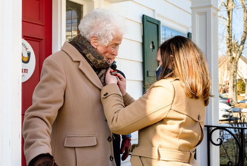 Emily Hemlow, Fund Development Manager, VON Nova Scotia, presents Joy Saunders with The Sovereign's Medal for Volunteers in a small private ceremony outside her Lunenburg home on Feb. 26. Contributed