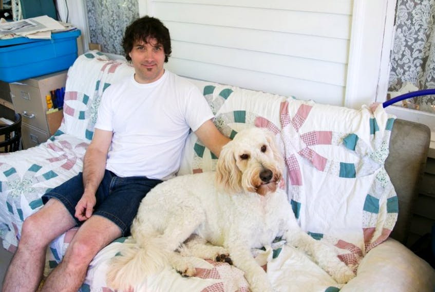 Matthew Collins sits in his sunroom with his dog Flossy. The Milton artist's work was recently purchased by the province for its art bank.