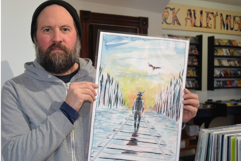 """Dennis Ellsworth, lead singer for The Fabulously Rich, a Tragically Hip tribute band, shows a print he purchased during a fundraising campaign for the Gord Downie and Chanie Wenjack Fund. It's by Jeff Lemire, the same artist who created the """"Secret Path"""" album cover for The Tragically Hip. However, instead of Wenjack walking on the railroad tracks, it's the late Gord Downie. Ellsworth says the tribute band will continue to support the fund. SALLY COLE/THE GUARDIAN"""