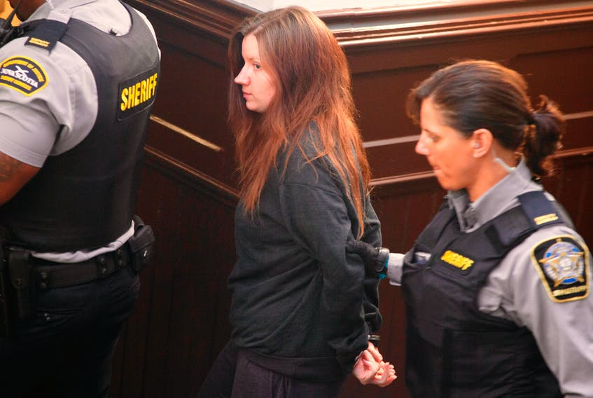 Victoria Henneberry is escorted from a courtroom at Halifax Provincial Court on Monday, July 21, 2014. The preliminary hearing got underway on Monday for Henneberry and her boyfriend Blake Leggette who are charged with first-degree murder in the death of Loretta Saunders. (RYAN TAPLIN/Staff)