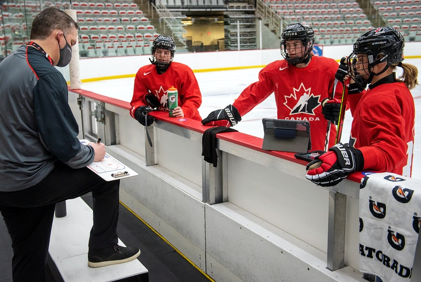 Blayre Turnbull of Stellarton (centre) and her linemates listen to Team Canada head coach Troy Ryan as he draws up a play during a national women's team training camp at WinSport Arena in Calgary on January. - Hockey Canada