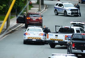 St. John's police shelter behind their vehicles at an apparent standoff scene on Craigmillar Ave. early Sunday morning. The RNC was called to the scene shortly after 4 a.m. and arrived to find the victim lying in the street, and a vehicle at the side of the road with the door open. Residents in the area were told to stay inside.