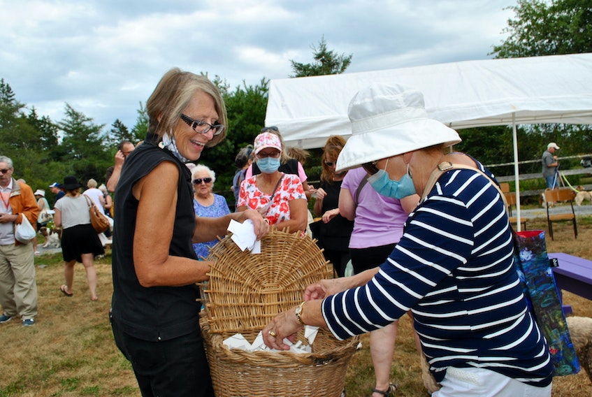 Ardra Cole (left), founder of ElderDog Canada gives out butterflies to be released in memory or in honour of canine companions at the ElderDog butterfly release in Lunenburg County on Aug. 15.