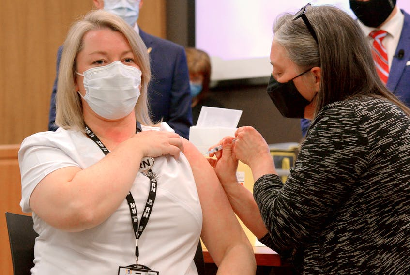 Ellen Foley-Vick (left), a registered nurse with public health, is given the first COVID-19 vaccination in the province by Chief Medical Officer of Health Dr. Janice Fitzgerald Wednesday afternoon. Keith Gosse/The Telegram