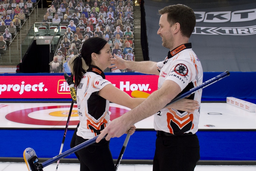Kerri Einarson and Brad Gushue hug after winning the 2021 Home Hardware Canadian Mixed Doubles Championship Thursday night in Calgary.