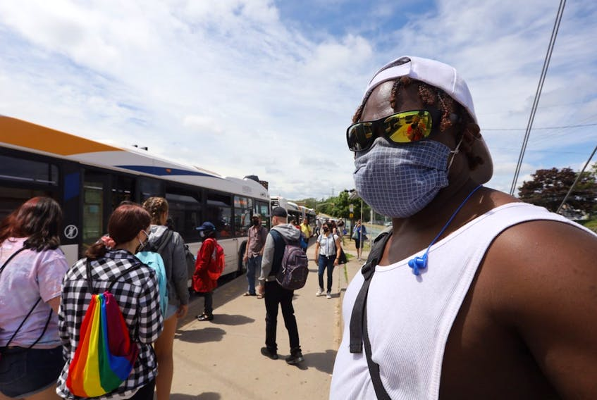 Halifax Transit passengers, many wearing masks, wait to board a bus at the Mumford Road terminal in west-end Halifax on July 17. After making them mandatory on public transit, Nova Scotia will make it mandatory to wear a non-medical mask in most public places beginning July 31.