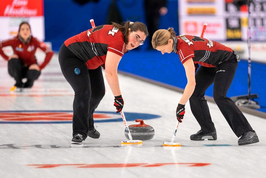 Newfoundland and Labrador's Lauren Barron (left) and Adrienne Mercer sweep a shot by skip Sarah Hill (background) during the Scotties Tournament of Hearts in Calgary. The N.L. team takes a 2-4 record into its final two round-robin games Thursday. — Andrew Klaver/Curling Canada