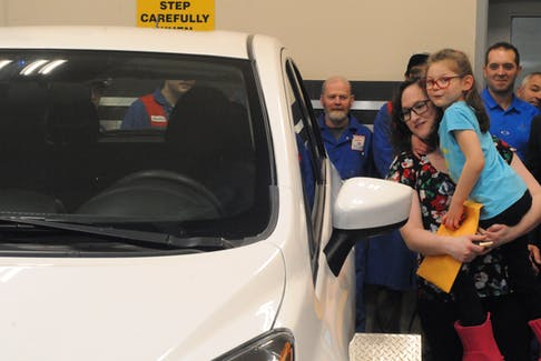 Above, Katherine Costello and daughter Maggie admire their new set of wheels. They received a free car courtesy of Collision Clinic in St. John's Wednesday – which also happened to be Maggie's seventh birthday.