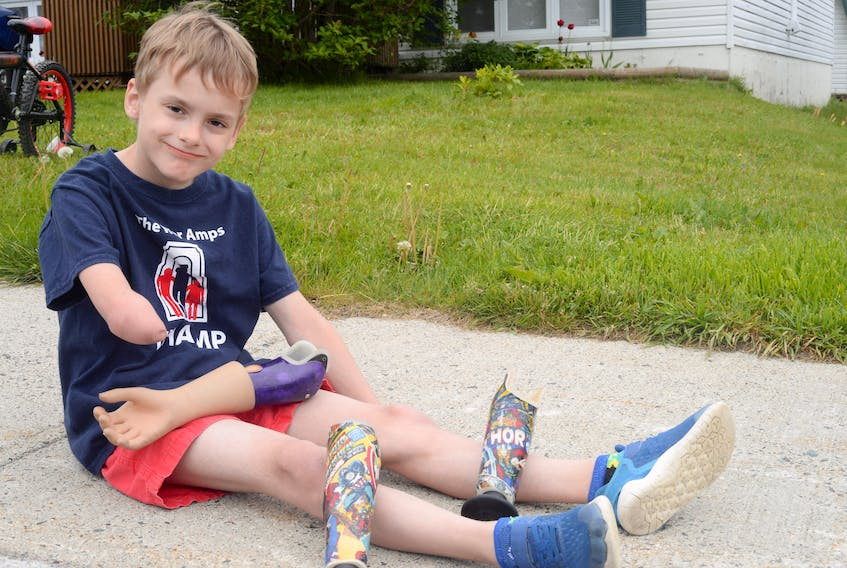 """Kirill Facey sat on the sidewalk in front of his home showing some of his specialized """"amputee arms."""" One of his arms is decorated with Spider-Man and Captain America."""