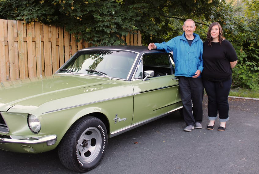 Harry (Herk) Phillips and his granddaughter, Stephanie Mealey, pose with a 1968 Mustang, one of a host of vintage cars that are located across Newfoundland and Labrador.