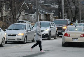 A pedestrian walks across a busy Thorburn Road in St. John's.