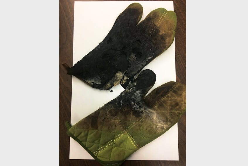 These ovens mitts, which were stored in the lower drawer of a stove, caught fire, causing significant smoke damage to a home in Burin. Burin Volunteer Fire Department's Facebook page