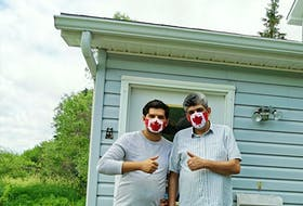 Samy and Ammar Hudhud pose for a photo at their home in Nova Scotia, where they moved in fall 2019. Leading up to Canada Day, the son and father duo crafted a couple hundred masks featuring Canada Day flags for people all over Canada to keep them safe and protected amid the COVID-19 pandemic.