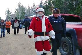 A protester dressed as Santa Claus is led away by the RCMP during the arrest of nine forestry operation blockaders Tuesday afternoon in Digby County.