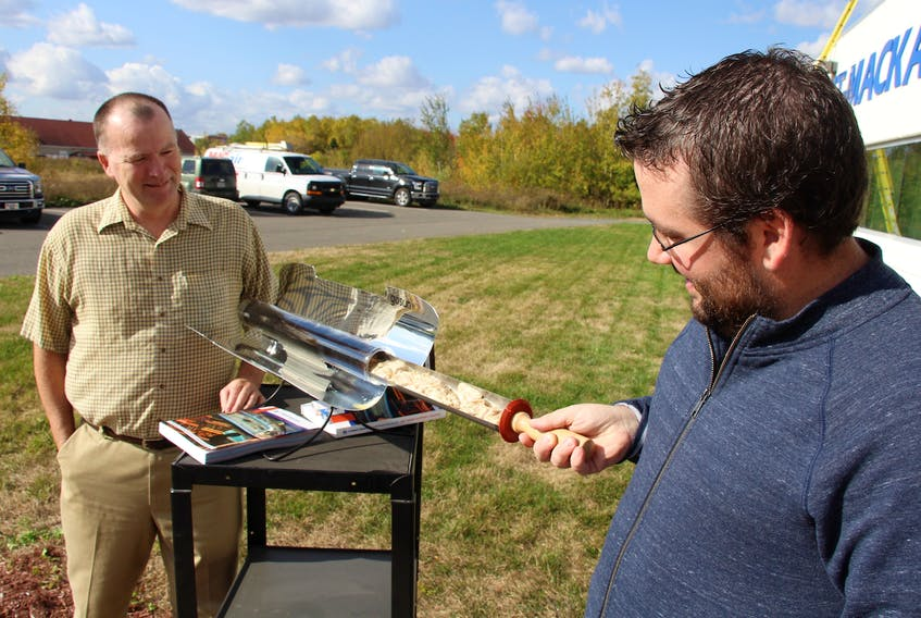 Peter Bennett, left, president of Stright-MacKay Ltd., and Eric Maldre of Stright-MacKay check chicken cooking in the GoSun Sport solar oven.   Stright-MacKay is the only marine dealer in the area distributing the new solar cookers that can prepare meals solely through the heat of the sun.