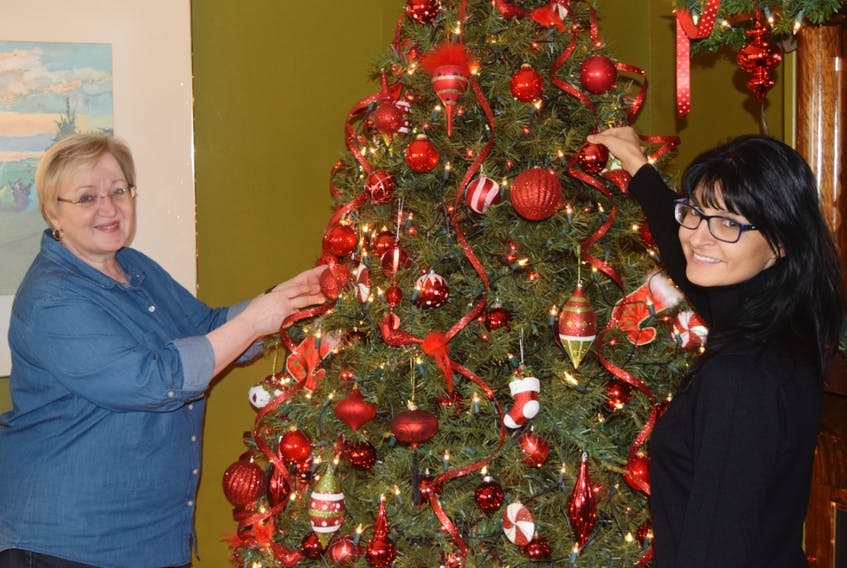 Jane Taylor and Stacey Pitts decorate one of several trees in Taylor's home in anticipation of the upcoming Christmas House Tour for Earth ARC. Taylor is one of several homeowners hosting the tour, in which they decorate their houses early, for the Christmas season.