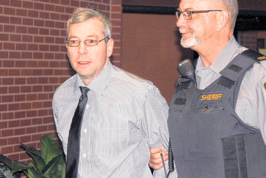 Leslie Greenwood is led into Supreme Court in Kentville Wednesday for his trial on two charges of first-degree murder in the deaths of Barry Mersereau and Nancy Christensen in September 2000.