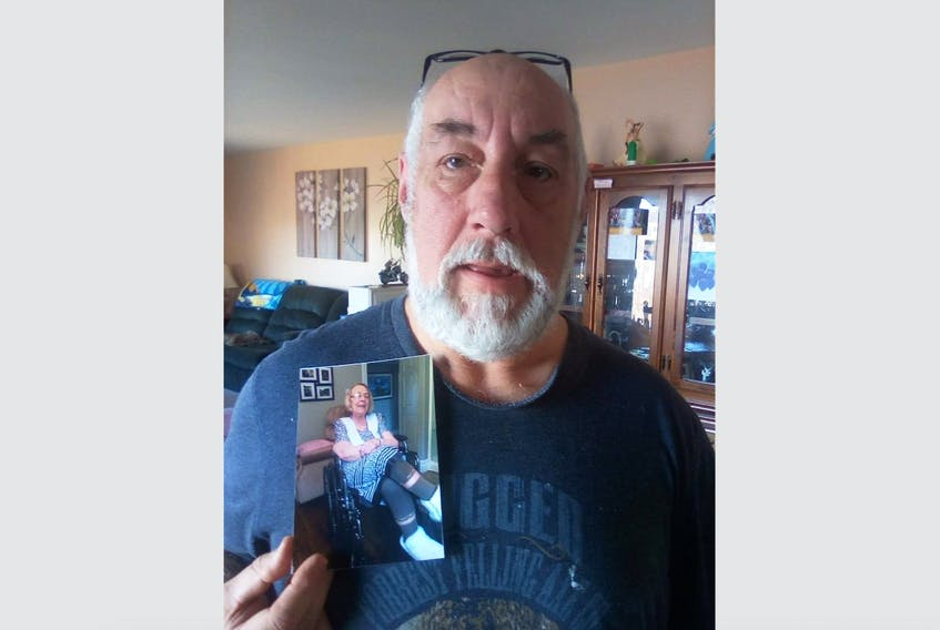 Morris Reid holds a picture of his mother, Mariam Reid. He says his mother has had to wait over a month for a procedure to remove gallstones and her health has deteriorated.