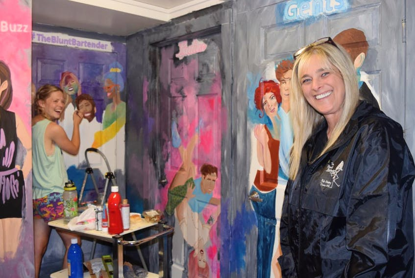 Cecilia McSwain, at left, is seen putting on the finishing touches to colourful murals that cover some of the walls inside Truro's newest pub, The Blunt Bartender, on Prince Street. Marie McDow, right, is the business owner.