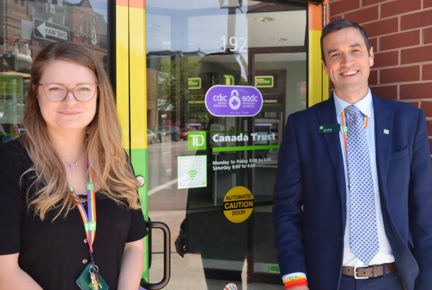 Jeff Likely, branch manager of TD Canada Trust in Charlottetown, and Emily Rooney, the branch's manager of customer experience, stand at the bank's entrance at the corner of Kent and Queen streets, which has been painted the colours of the rainbow to show the company's pride in the 2SLGBTQIA+ community.
