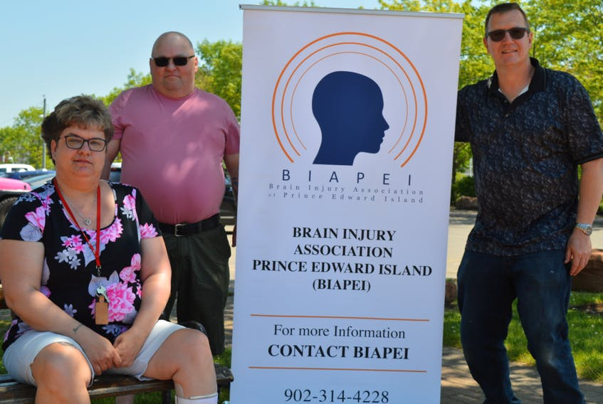 Simon Micklethwaite, right, president of the Brain Injury Association of P.E.I., says the group plans to offer more peer support help and hopes to find locations across the province to meet with clients. He's pictured with board members, Wendi Plets and Elton Poole.