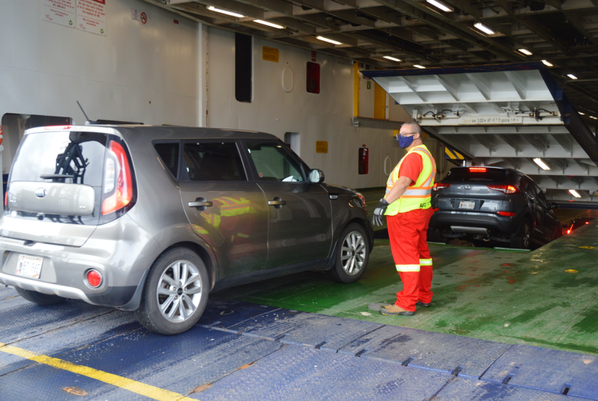 A worker with Northumberland Ferries Ltd. supervises the vehicles driving onto the MV Confederation ferry at the Wood Islands, P.E.I., terminal on Friday morning. - Dave Stewart/SaltWire Network