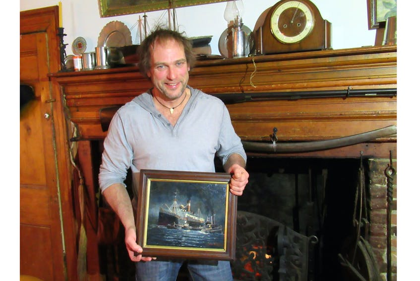 Celebrated marine artist Yves Bérubé displays one of his smaller oil paintings in front of the original fireplace in his circa 1771 Rose Bay home. Peter Simpson Photo