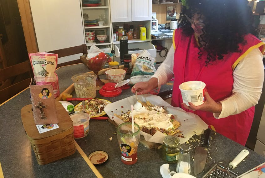 Moyra Boone prepares a pan of nachos during an episode of The Singing Chef. The Sackville, N.B. woman offers three shows a week to her followers on social media.
