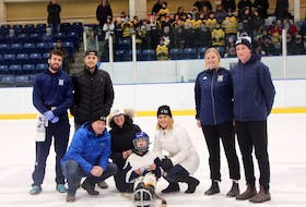 """Representatives for the Bulldog sledge hockey program and Bonvie-MacDonald Rinks to Links came together for a photo as Rinks to Links presented sledge hockey player Daniel Bond with a commitment to purchase for him a personalized sled designed for """"the more competitive player who is ready to reach the next stage of their development."""" Pictured is; Giovanni Akeson (standing, left), Liam Saxon, Abby MacInnis, Brent Ashfield, Chris Dunlap (kneeling, left), Denise Hart and Nicole Mann, and, out front, eight-year-old Daniel. In the background in the stands are Antigonish Minor Hockey Association novice players who play hockey with Daniel as part of the program."""